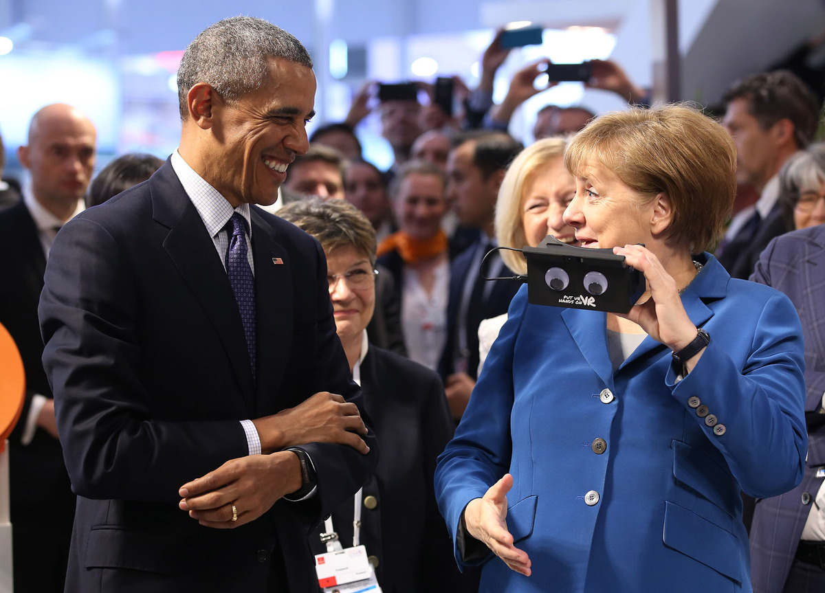 U.S. President Barack Obama, left, and German chancellor Angela Merkel test VR goggles when touring the Hannover Messe, the world's largest industrial technology trade fair, in Hannover, northern Germany, Monday, April 25, 2016. Obama is on a two-day official visit to Germany. (Christian Charisius/dpa via AP)